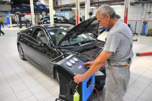 На фото - заправка кондиционера авто в автосервисе, dvklimat.ru