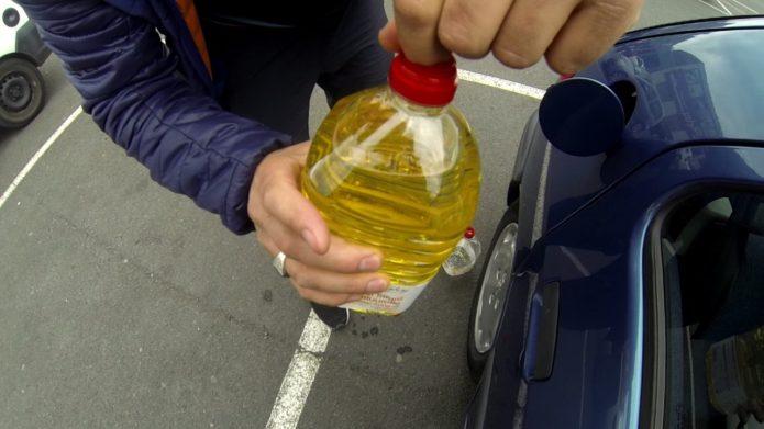 Растительное масло в руках и человек у бензобака