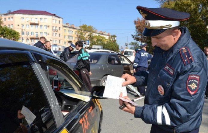 Сотрудник ГИБДД проверяет документы